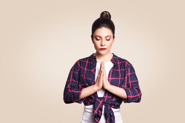 Jovem morena praticando ioga, segurando as mãos em namastê e mantendo os olhos fechados. menina caucasiana meditando dentro de casa, orando por paz e amor, tendo uma expressão facial calma e pacífica.
