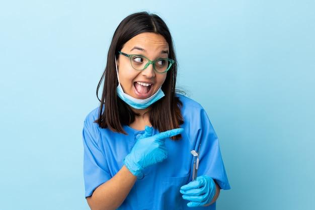 Jovem morena raça mista dentista mulher segurando ferramentas