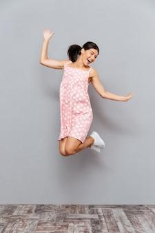 Jovem morena rindo, pulando sobre uma parede cinza
