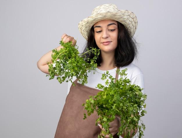 Jovem morena satisfeita com um jardineiro de uniforme, usando chapéu de jardinagem, segurando e olhando para o coentro isolado na parede branca