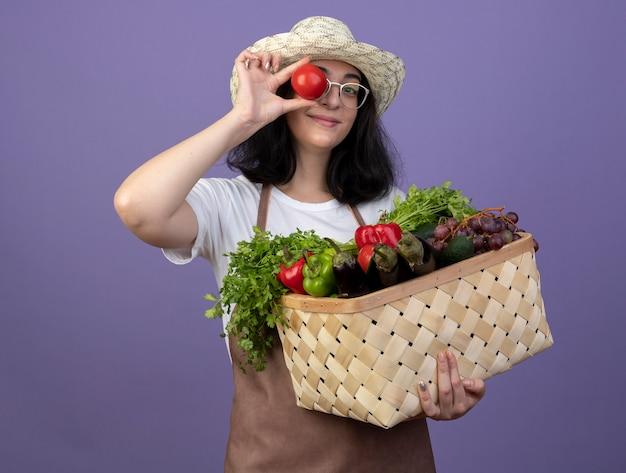 Jovem morena satisfeita com um jardineiro feminino de óculos e de uniforme, usando um chapéu de jardinagem, segurando uma cesta de vegetais e cobrindo o olho com tomate isolado na parede roxa