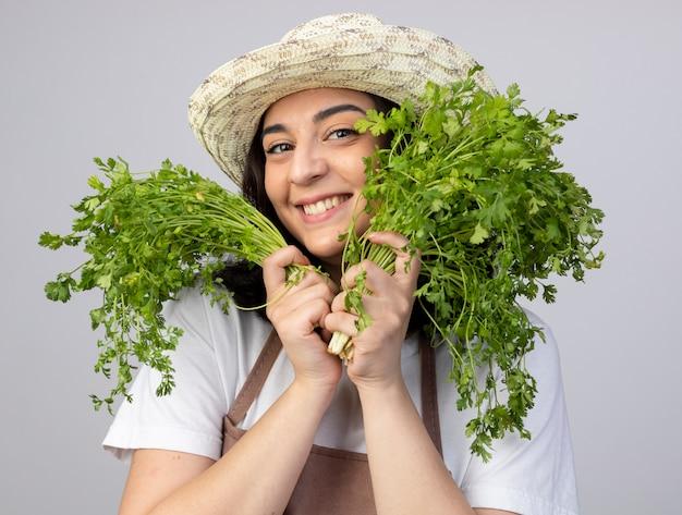 Jovem morena satisfeita com um jardineiro uniforme, usando um chapéu de jardinagem, segurando coentro isolado na parede branca com espaço de cópia