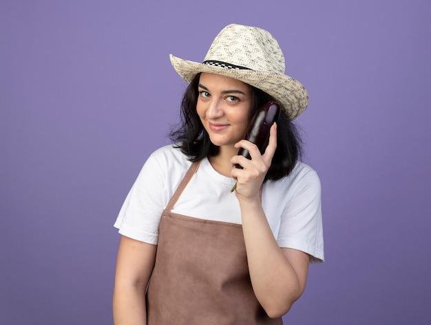 Jovem morena satisfeita com uma jardineira de uniforme, usando um chapéu de jardinagem, segurando uma berinjela isolada na parede roxa