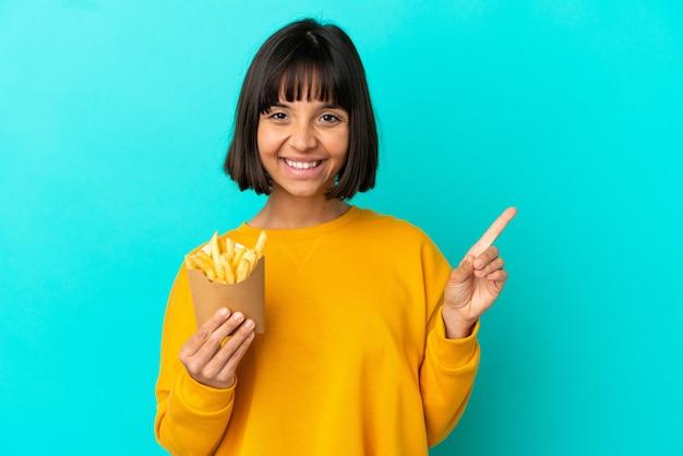 Jovem morena segurando batatas fritas sobre um fundo azul isolado, apontando para o lado para apresentar um produto