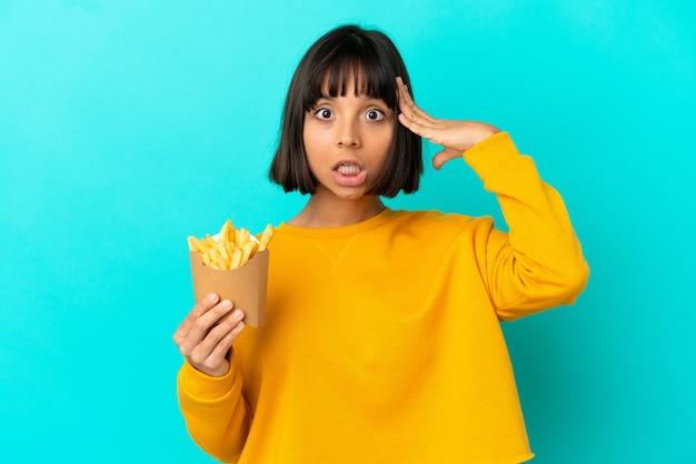 Jovem morena segurando batatas fritas sobre um fundo azul isolado com expressão de surpresa