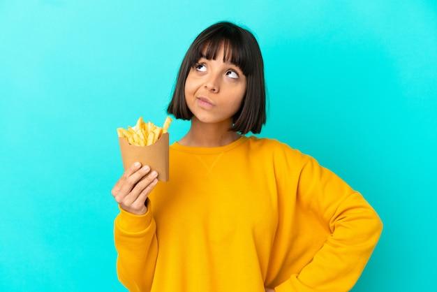 Jovem morena segurando batatas fritas sobre um fundo azul isolado e olhando para cima