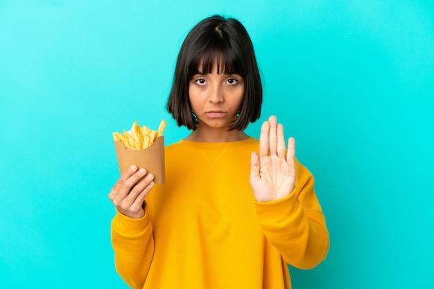 Jovem morena segurando batatas fritas sobre um fundo azul isolado, fazendo um gesto de pare