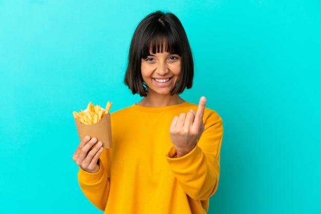 Jovem morena segurando batatas fritas sobre um fundo azul isolado, fazendo um gesto próximo