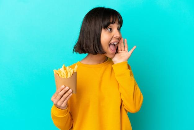 Jovem morena segurando batatas fritas sobre um fundo azul isolado, gritando com a boca aberta para o lado