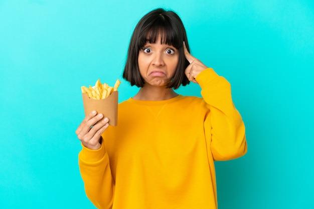 Jovem morena segurando batatas fritas sobre um fundo azul isolado, pensando em uma ideia.