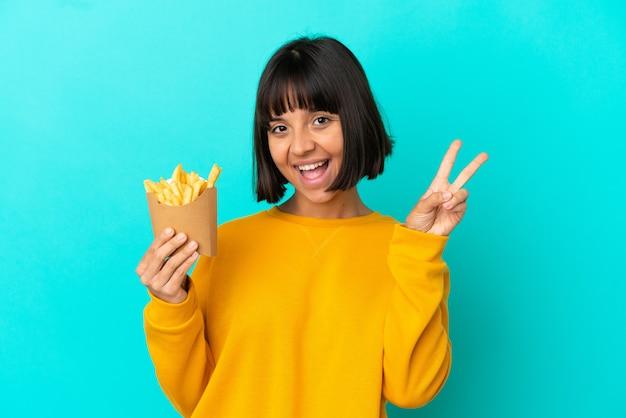 Jovem morena segurando batatas fritas sobre um fundo azul isolado, sorrindo e mostrando o sinal da vitória