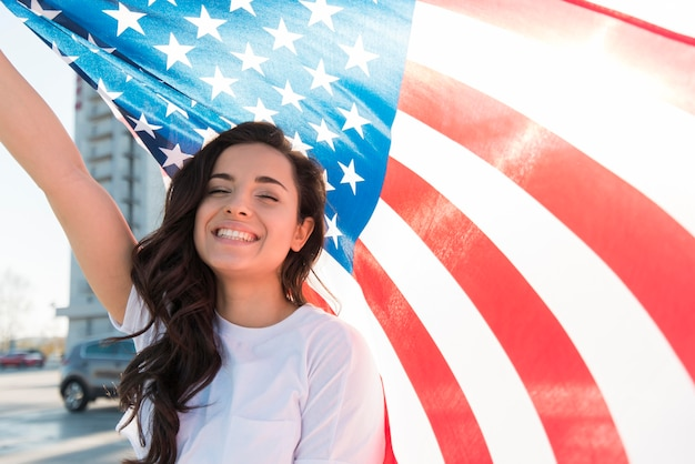 Jovem morena segurando grande bandeira dos eua e sorrindo
