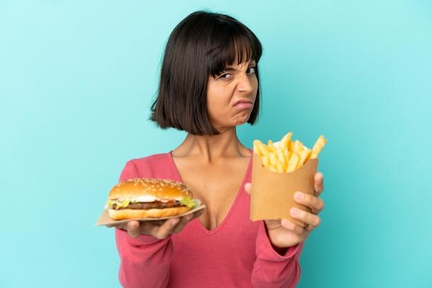 Jovem morena segurando hambúrguer e batatas fritas sobre fundo azul isolado