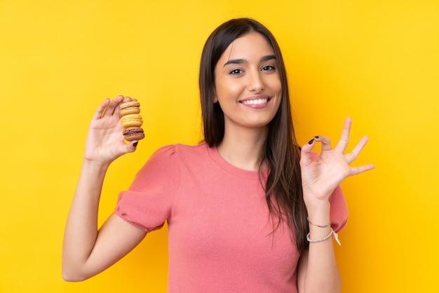 Jovem morena segurando macarons franceses coloridos e mostrando sinal de ok com os dedos