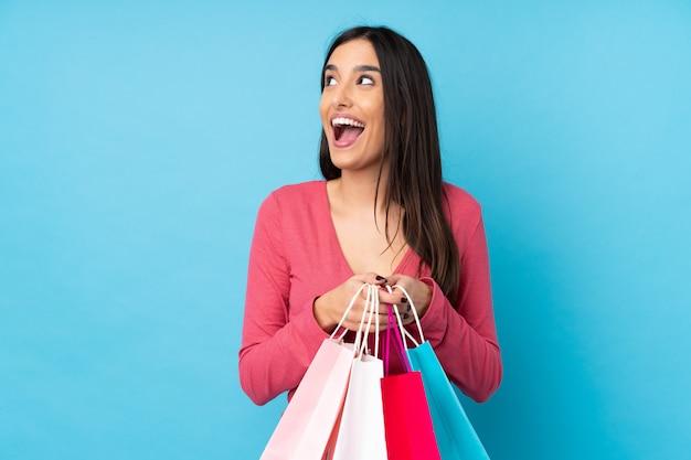 Jovem morena segurando sacolas de compras e surpreso
