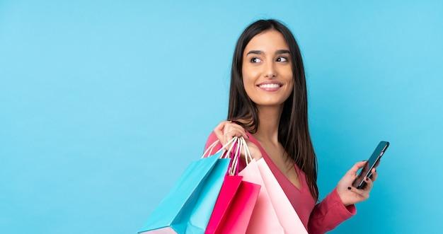 Jovem morena segurando sacolas de compras e um telefone celular