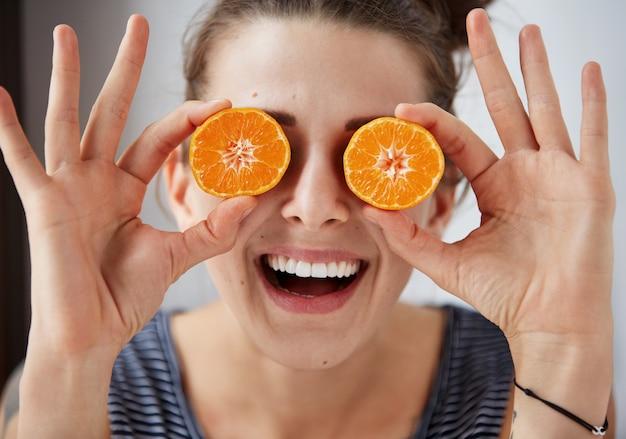 Jovem morena segurando tangerinas em vez de olhos, rindo e aproveitando a vida