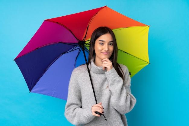Jovem morena segurando um guarda-chuva sobre parede azul isolada rindo
