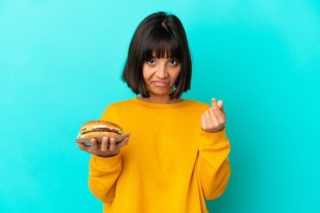 Jovem morena segurando um hambúrguer sobre um fundo isolado, fazendo gesto de dinheiro