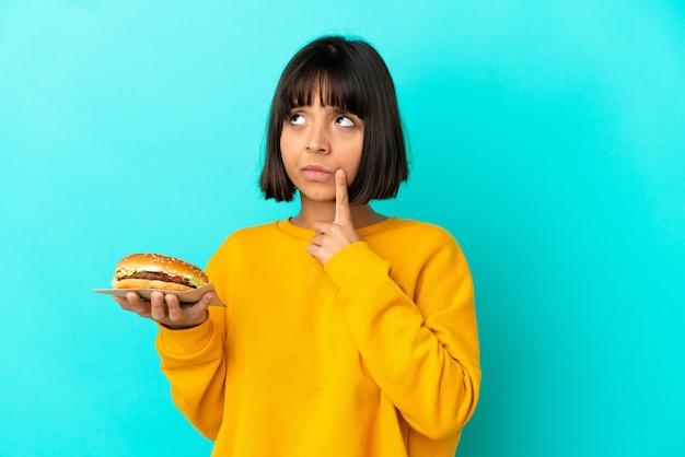 Jovem morena segurando um hambúrguer sobre um fundo isolado, tendo dúvidas enquanto olha para cima