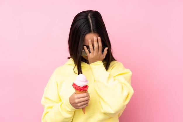 Jovem morena segurando um sorvete de corneta sobre parede rosa isolada com expressão cansada e doente