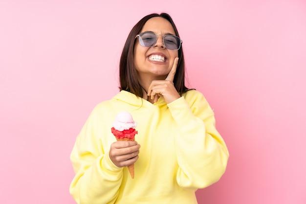 Jovem morena segurando um sorvete de corneta sobre um rosa isolado sorrindo com uma expressão feliz e agradável