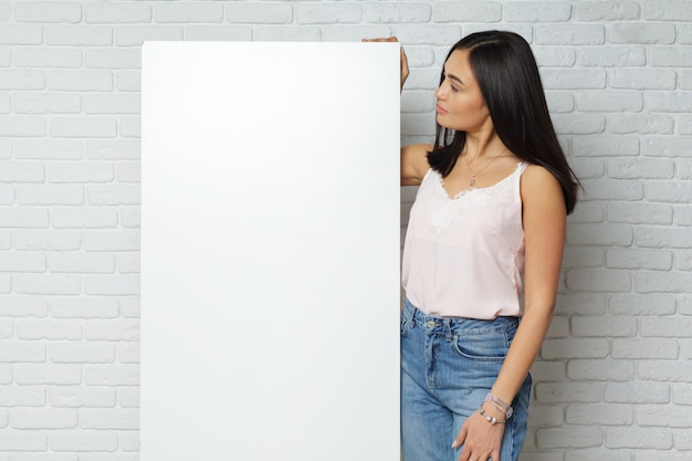 Jovem morena segurando uma grande placa branca em branco, com espaço de cópia