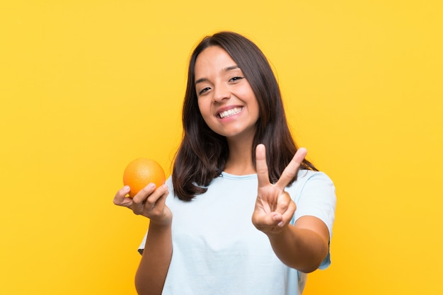 Jovem morena segurando uma laranja sorrindo e mostrando sinal de vitória