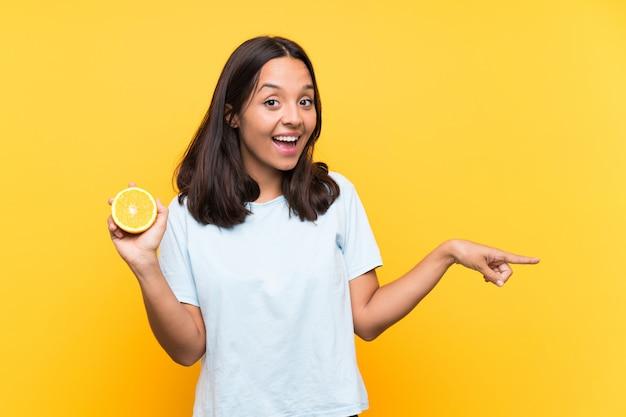Jovem morena segurando uma laranja surpreendeu e apontando o dedo para o lado