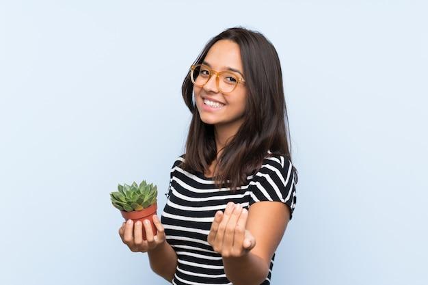 Jovem morena segurando uma planta convidando para vir com a mão