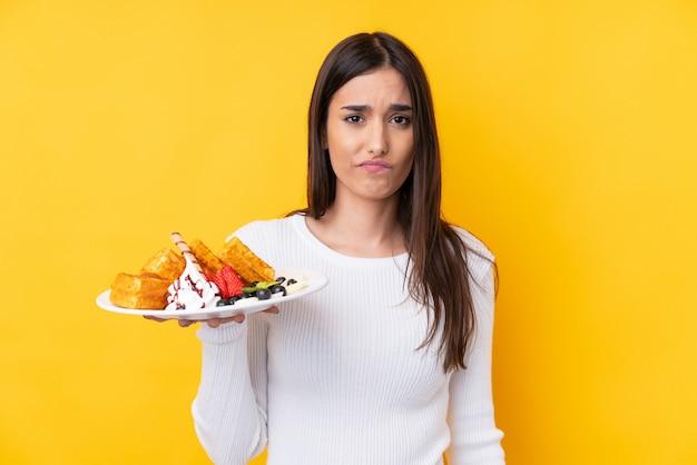 Jovem morena segurando waffles com expressão triste