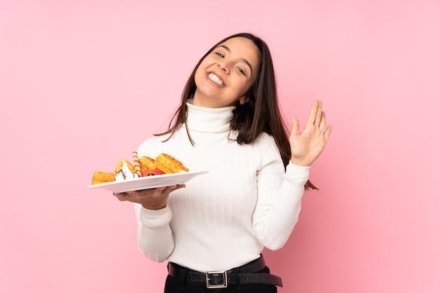Jovem morena segurando waffles em uma saudação rosa isolada com a mão e expressão feliz