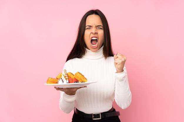 Jovem morena segurando waffles isolados, frustrada por uma situação ruim