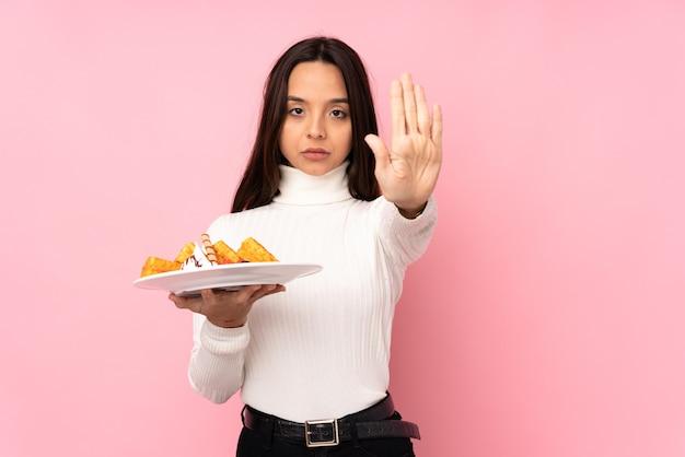 Jovem morena segurando waffles isolados