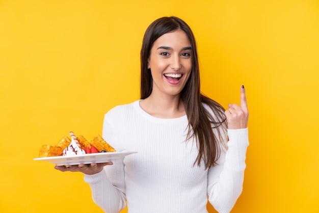 Jovem morena segurando waffles sobre parede isolada, apontando para cima uma ótima idéia