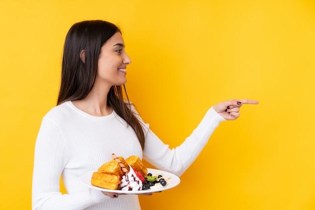 Jovem morena segurando waffles sobre parede isolada, apontando para o lado para apresentar um produto