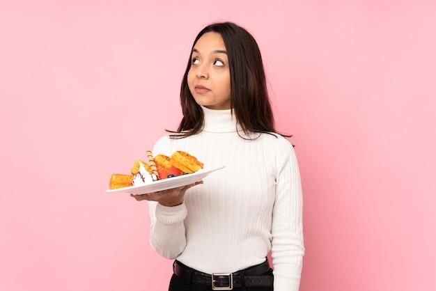 Jovem morena segurando waffles sobre rosa, fazendo um gesto de dúvida, olhando para o lado