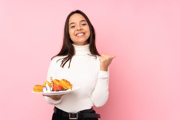 Jovem morena segurando waffles sobre uma parede rosa isolada apontando para o lado para apresentar um produto