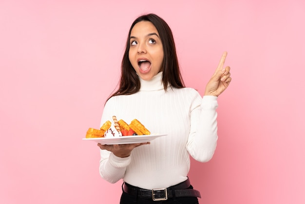 Jovem morena segurando waffles sobre uma parede rosa isolada com a intenção de descobrir a solução enquanto levanta um dedo