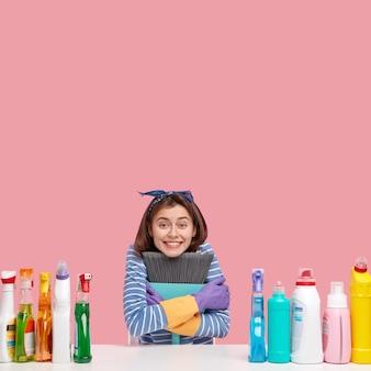Jovem morena sentada ao lado de produtos de limpeza