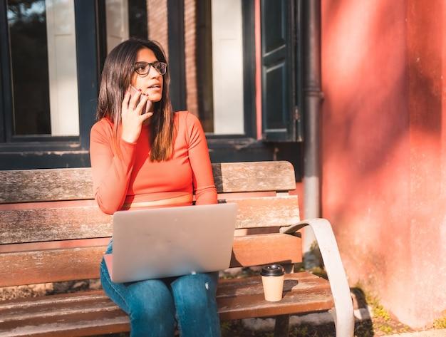Jovem morena sentada em um banco no parque com laptop