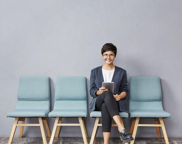 Jovem morena sentada na cadeira segurando um tablet