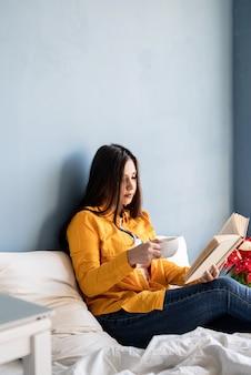 Jovem morena sentada na cama comendo croissants e lendo um livro