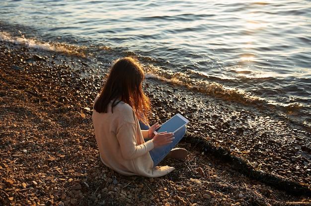 Jovem morena sentada na praia, ao pôr do sol, lendo no tablet