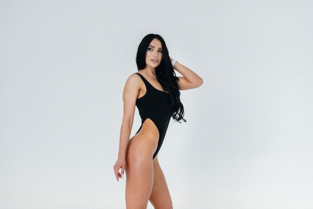 Jovem morena sexy em uma roupa preta sobre fundo branco. a figura atlética perfeita.