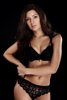 Jovem morena sexy sobre fundo preto