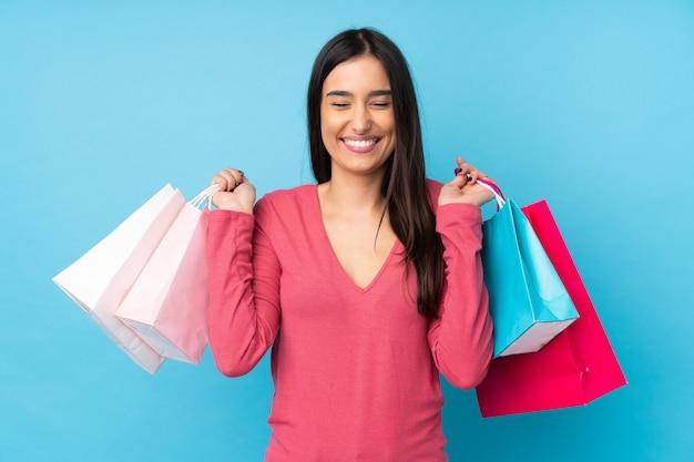 Jovem morena sobre azul segurando sacolas de compras e sorrindo