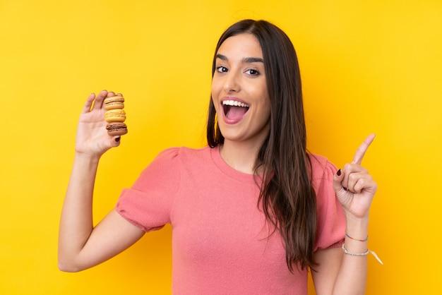 Jovem morena sobre parede amarela isolada segurando macarons franceses coloridos e apontando uma ótima idéia