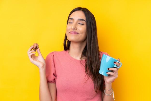 Jovem morena sobre parede amarela isolada segurando macarons franceses coloridos e um copo de leite