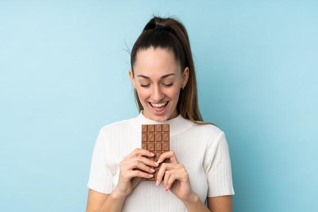 Jovem morena sobre parede azul isolada, comendo uma tablete de chocolate